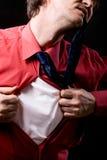 Erzürnter Mann zerreißt weg ein rotes Hemd auf einem schwarzen Hintergrund Stockfotografie