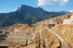Erzberg iron mine with mountains. Erzberg iron mine with mountains in the background. In front, twisty road trough the mine. On one of the platforms to the left Stock Photography