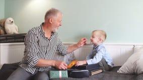 erzeugung Großvater und Enkel mit der Geschenkbox, die zu Hause auf Couch sitzt stock footage
