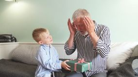 erzeugung Großvater und Enkel mit der Geschenkbox, die zu Hause auf Couch sitzt stock video