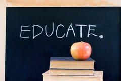ERZIEHEN Sie auf Tafel mit Apfel u. Büchern Lizenzfreies Stockbild