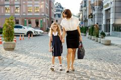Erziehen Sie das Halten eines Kindes durch die Hand, gehen Sie zur Schule Stockfotografie