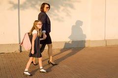 Erziehen Sie das Halten eines Kindes durch die Hand, gehen Sie zur Schule Lizenzfreie Stockfotografie