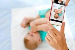 Erziehen Sie das Machen des Fotos eines Babys mit Smartphone Entzückendes neugeborenes Kind, das Fuß im Mund nimmt Lizenzfreie Stockfotos