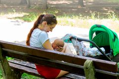 Erziehen Sie Krankenpflegekind öffentlich, hübsche Mutter sich interessiert leicht ihr kleines Baby in den Händen und ihn mit Lie Lizenzfreie Stockfotos