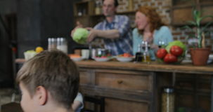 Erzieht das Kochen der Mahlzeit, während Kinder Gebrauchs-Tablet-Computer bei Tisch sitzen essen, glückliche Familie in der Küche stock video