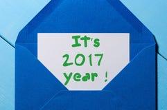 Es 2017 años - letra de la inspiración en sobre azul Fondo de las Felices Año Nuevo y de la Navidad Imagenes de archivo