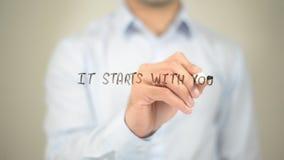 Es beginnt mit Ihnen, Mannschreiben auf transparentem Schirm stockfotografie