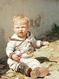 Es gibt das Kind, das auf einem Gartenweg sitzt Stockbilder