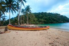 Es gibt ein altes orange Kanu auf dem Sand stockbild