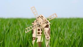 Es gibt eine kleine Windmühle im grünen Weizengras Das Konzept der Landwirtschaft, der Agronomie, des Erntens und der Bearbeitung stock footage