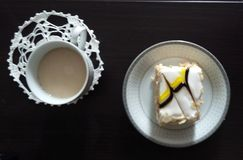 Es gibt eine Schale mit Cappuccino und eine Platte mit Kuchen Lizenzfreie Stockbilder