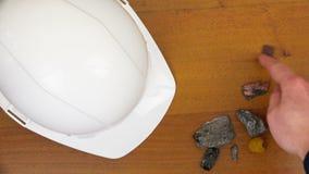 Es gibt einen weißen Sturzhelm und Steine auf dem Tisch stock video footage