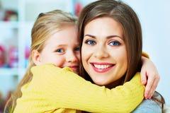 Es gibt 3 Mädchen und ihre Mutter, die auf der orange Couch sitzen Mutter, Tochter… Lächeln, Glück und Hoffnung Glückliches Mädch Stockfoto