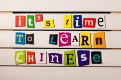 Es hora de aprender el chino - escrito con recortes de la letra de la revista del color en el tablero de madera Aprendizaje de id Foto de archivo libre de regalías
