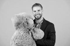 Es ist nie zu spät, glückliches Erwachsensein zu haben Mann hols großer Teddybär, grauer Hintergrund Geburtstagsgeschenkkonzept t stockfotografie