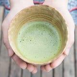 Es movimiento para sostener té verde hacia fuera pulverizado Imagen de archivo
