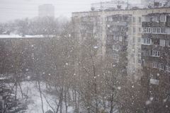 Es schneit außerhalb des Fensters auf dem Hintergrund der Stadt Lizenzfreie Stockfotografie
