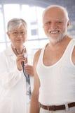 Esame attendente sorridente dell'uomo anziano immagini stock