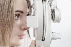 Esame degli occhi aspettante della donna con phoropter immagine stock libera da diritti