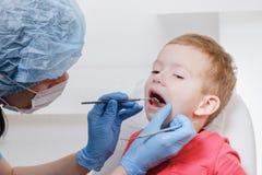 Esame del dentista dei denti pazienti del bambino facendo uso di uno specchio della carie dello strumento, danno del dente, malat fotografia stock libera da diritti