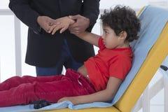 Esame del polso per il sintomo del bambino di dolore fotografia stock libera da diritti