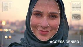 Esame futuristico e tecnologico del fronte di bella donna nel hijab per riconoscimento facciale ed esplorato archivi video