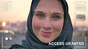 Esame futuristico e tecnologico del fronte di bella donna nel hijab per riconoscimento facciale ed esplorato stock footage