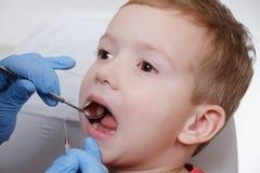 Esame medico dei denti pazienti del bambino facendo uso di uno specchio da un dentista Caries, danno del dente fotografie stock