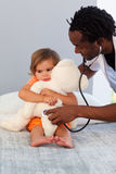 Esami del pediatra una bambina con lo stetoscopio Immagine Stock
