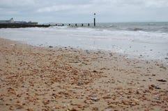 Esaminando giù la spiaggia un frangiflutti che sta sporgendosi nel mare Immagini Stock
