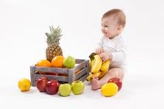Esaminando il bambino sorridente sveglio della frutta su fondo bianco fra i frutti fotografia stock