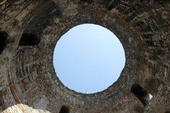 Esaminando il cielo attraverso il foro di una torre antica Immagine Stock