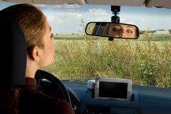 Esaminando lo specchio retrovisore. Fotografia Stock