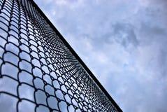 Esaminando in su un cielo minaccioso dietro una rete fissa alta Immagine Stock