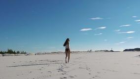 Esamini da dietro la donna castana in cima bianca e biancheria nera che cammina sulla sabbia sotto il cielo blu stock footage