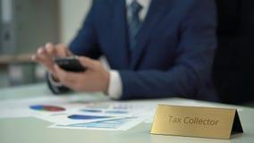 Esattore delle tasse che utilizza smartphone sul lavoro, controllante le statistiche di debito nei diagrammi stock footage