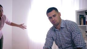 Esaurimento nervoso, uomo infelice nella scossa dal giurare con la moglie furiosa durante la psicosi con i gesti aggressivi stock footage