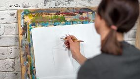 Esbo?o do desenho da mulher do pintor na lona usando a opini?o cinzenta da parte traseira do close-up do l?pis filme