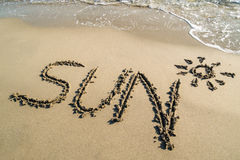 Esboço do sol do texto no Sandy Beach molhado Fotografia de Stock