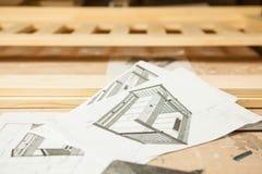 Esboços da cama de madeira em pedaços de papel no fundo de madeira Foto de Stock