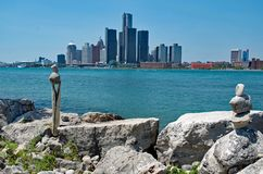 Escénico de Detroit tomado de Canadá con las pilas de piedras o de mojón en primero plano foto de archivo libre de regalías