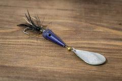 Esca di cucchiaio, richiami, mosche, attrezzatura per pescare o la pesca del pesce predatore sul fondo di legno della piattaforma Immagini Stock