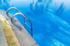Escada da barra da piscina na luz - água azul Imagem de Stock