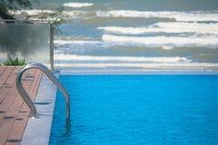 Escada da barra de garra do metal na piscina da água azul com fundo da onda do mar Fotos de Stock Royalty Free