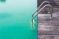 Escada de aço velha, tábuas corridas de madeira e piscina verde Foto de Stock Royalty Free