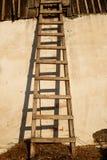 Escada de madeira velha com sombra perto da parede emplastrada whitewashed da casa envelhecida fotografia de stock royalty free