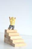 Escada do conceito do sucesso com um homem sobre escadas de madeira dos blocos Imagens de Stock Royalty Free