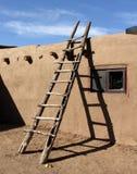 Escada do sudoeste que inclina-se contra a parede do adôbe no povoado indígeno de Taos fotografia de stock