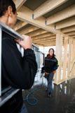 Escada levando de Looking At Colleague do carpinteiro em Bui incompleto Imagens de Stock
